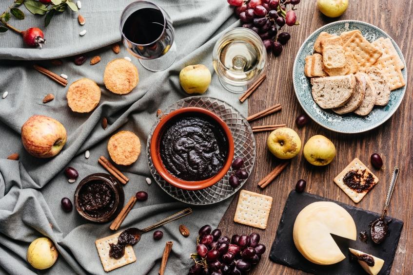 Fotografia de uma mesa com uvada, queijo, torradas e vinho tinto da região. Fotografia de Emanuele Siracusa. Styling por Yuliya Pinheiro